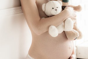 Pregnant female holds baby soft toys