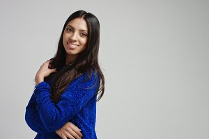 Attractive Latino female model in warm bright blue sweater