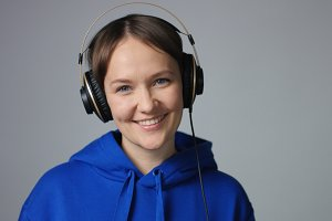 Beautiful woman in blue hoodie putting on headphones