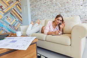 young beautiful woman is sitting on a sofa on a white brick wall background with a cup of coffee. Laptop, documents, drawings. Girl freelancer is resting.