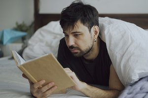 Handsome young man reading a book lying in bed under blanket at home