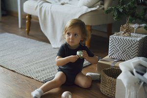 Adorable little girl playing with toy balls sitting near Christmas tree at home