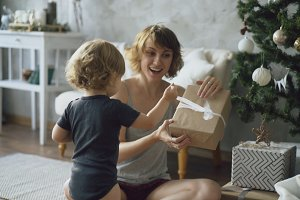 Happy mother and her little daughter unpack gift box near the Christmas tree at home