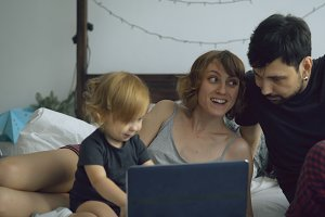 Young family with cute little girl playing with daughter while she typing on laptop computer sitting in bed at home