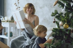 Happy family with little daughter decorating Christmas tree at home