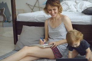 Happy mother with cute adorable daughter drawing in album with pencils sitting near bed at home