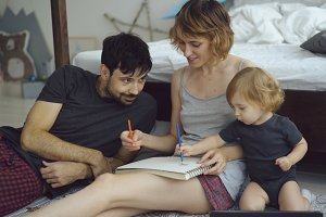 Happy family with cute adorable daughter drawing in album with pencils sitting near bed at home
