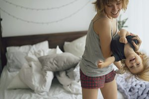 Happy young mother and little cute daughter dancing near bed in bedroom at home