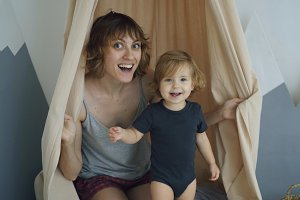 Happy mother with young cute daughter playing and and hide behind curtain at home