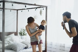 Happy family and little cute daughter dancing near bed in bedroom while famter singing at home