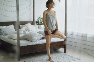 Young beautiful woman doing yoga exercise near bed in bedroom at home