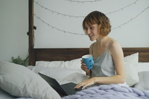 Cheerful young woman having video chat with friends using laptop camera while sitting on bed at home