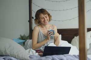 Attractive cheerful woman having online video chat with friends using laptop camera while sitting on bed at home