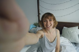 Young cheerful woman taking selfie portrait using smartphone sitting in bed in at home