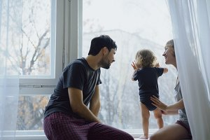 Happy family with young cute daughter sitting on windowsill playing and looking in window at home
