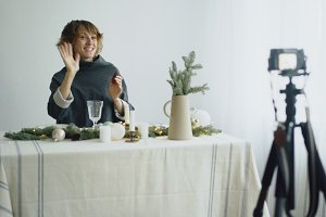 Attractive cheerful woman sitting at the table recording video blog about table setting design on camera