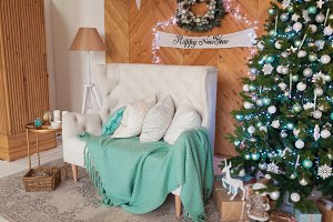 New Year's interior in turquoise color. White sofa, Christmas tree with gifts