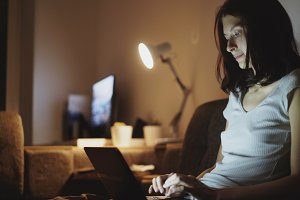 Young attractive woman sharing social media using on laptop computer at home in night time