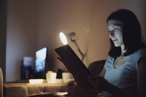 Young attractive woman using tablet computer for online shopping at home at night