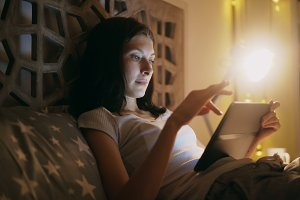 Close-up of young concentrated woman using tablet and watching online news lying in bed at home at night