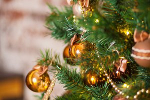 Golden and brown balls on the Christmas tree. Close-up