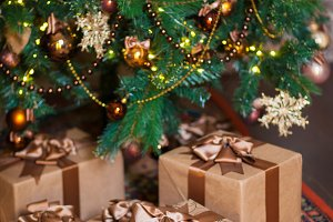 Brown boxes with Christmas gifts on the background of a Christmas tree