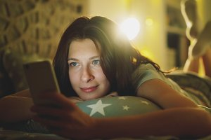 Attractive smiling woman using smartphone for sharing social media lying in bed at home at night