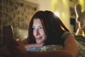 Young smiling woman using smartphone for sharing social media lying in bed at home at night
