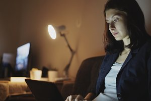 Young concentrated woman working at night using laptop computer and typing message