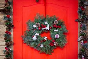 Christmas wreath made of spruce branches, red balls, cones on the wooden background