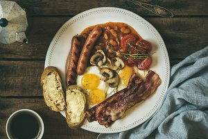 English breakfast with fried eggs, sausages, mushrooms, bacon, beans, coffee