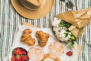 Flat-lay of rose wine, strawberries, croissants, brie cheese, peony flowers