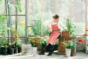 Young cute lady working at the greenhouse