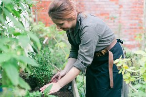 Young cute lady working at the garden