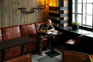 Young man sitting alone in loft-styled cafe.