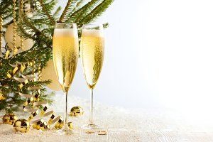 Two glasses of champagne ready to bring New Year on Christmas tree background