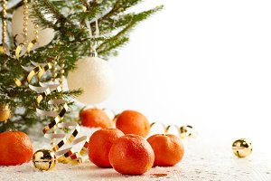 Christmas tree with tangerines on white snow background