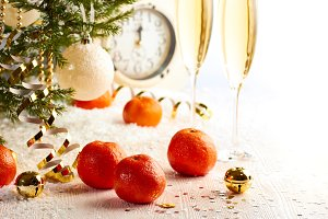 Christmas tree with tangerines, champagne and clock