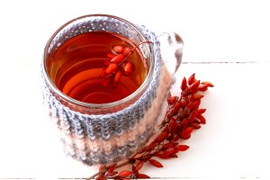 barberry tea with a knitted mug isolated on a white background