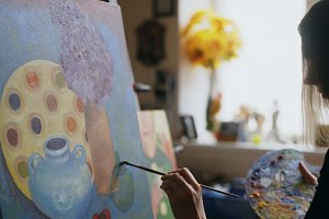 Close-up of woman artist painting still life picture on canvas in art studio