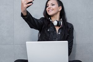 Woman with laptop taking selfie