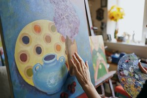 Woman artist smearing oil paints on canvas picture in art workshop