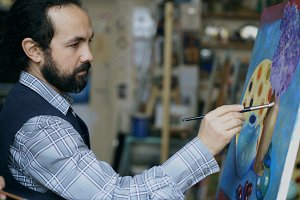 Concentrated man artist painting still life picture on canvas in art studio indoors