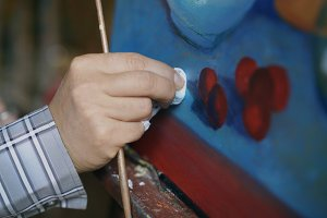 Close-up of artist's hand smearing oil paints on canvas picture in art workshop