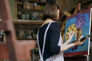 Talented young woman artist painting picture on canvas in art-class