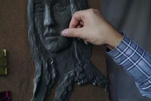 Close-up of Sculptor creating sculpture of woman's face on canvas in art studio