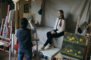 Sculptor creating sculpture of human's face on canvas while young woman posing to him in art studio