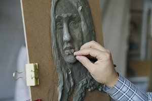 Close-up of Sculptor creating sculpture of human's face on canvas while young woman posing to him in art studio