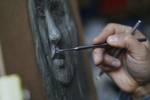 Close-up of Sculptor creating sculpture of human's face on canvas in art studio