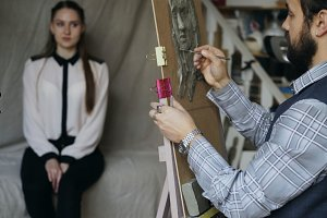 Sculptor creating sculpture of human's face on canvas while young woman posing him in art studio